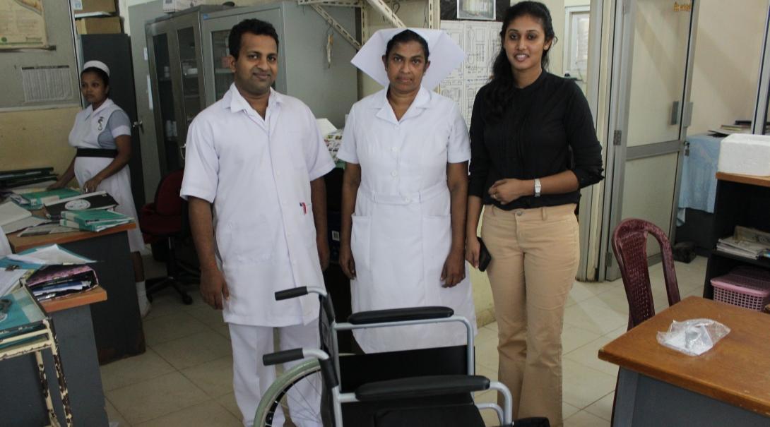 Doctores locales e interna de fisioterapia posan junto a una silla de ruedas donada por Projects Abroad en Sri Lanka.